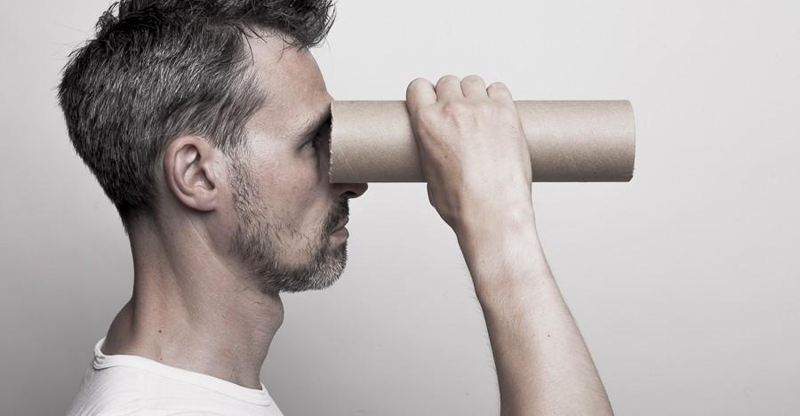 Mann schaut mit dem rechten Auge in ein Papprohr das er mit seiner rechten Hand festhält