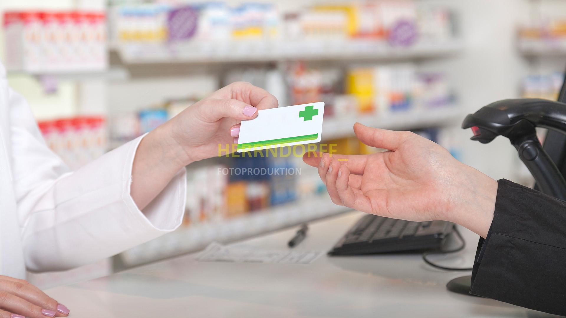 Apothekerin händigt einer Kundin eine Kundenkarte aus