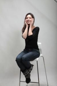 Brünettes Fotomodell sitzt auf einem Barhocker beim Casting und hält sich ihre Hände an die Wangen