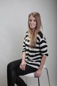 Blondes Fotomodell sitzt auf einem Barhocker im Studio
