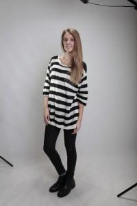 Blondes Fotomodell in schwarzer Lederhose und schwarz-weiss gestreiften Schlabberpullover beim Casting im Fotostudio