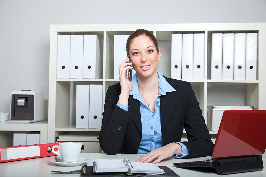 Sympathische Frau telefoniert am Arbeitsplatz im Büro | Herrndorff Fotoproduktion | Stockfotoblog.de