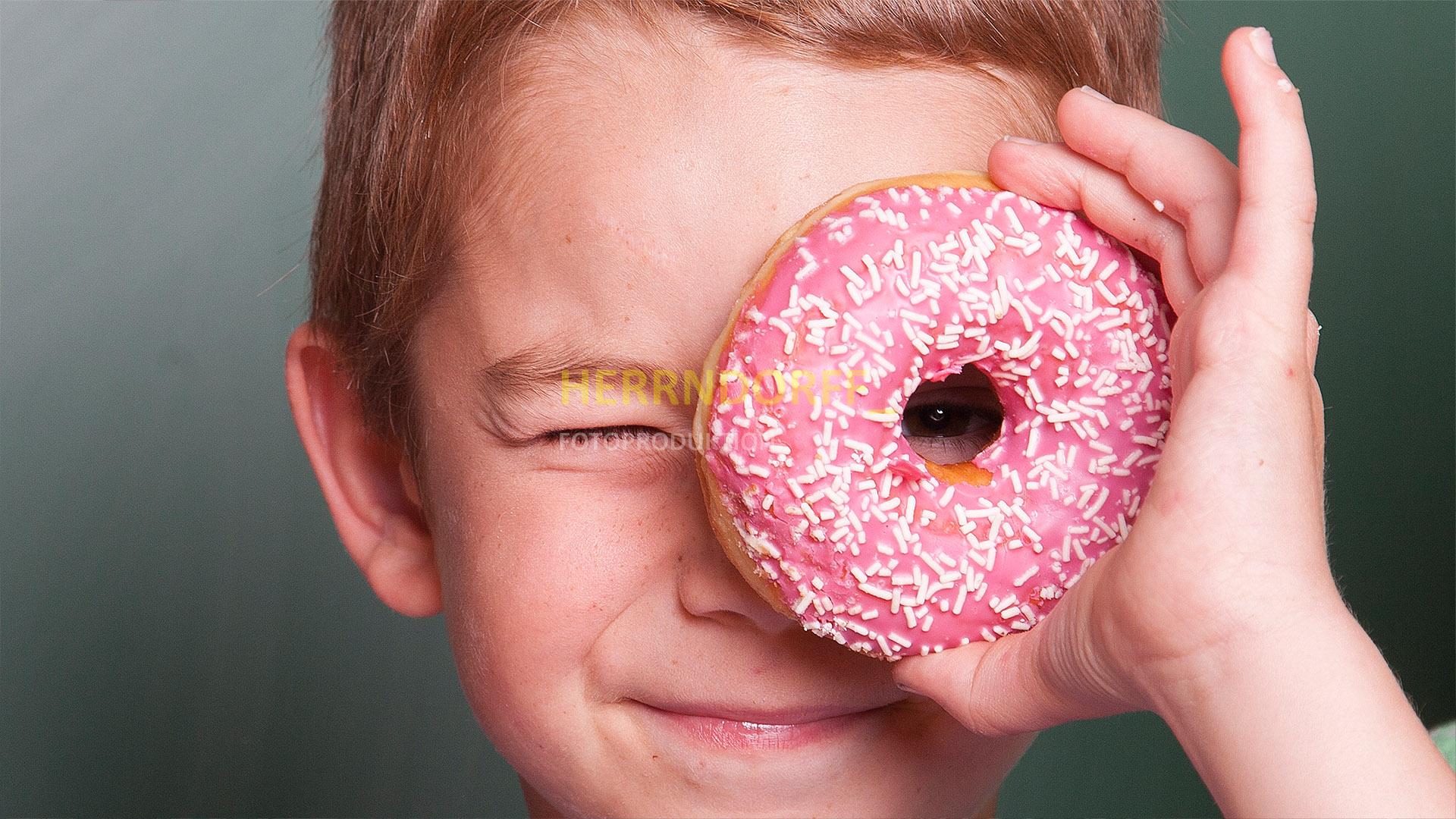 Kleiner Junge sieht durch das Loch seines Erdbeer-Donut