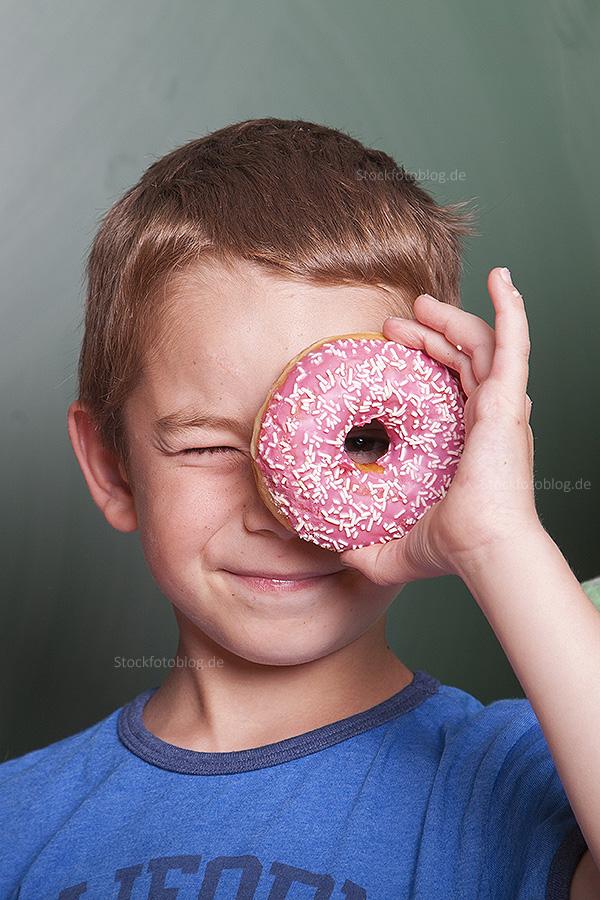Grundschüler vor Tafel schaut durch seinen Donut