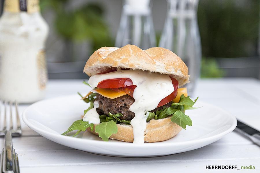 Saftiger frischer Hamburger mit Rindfleisch Fikadelle, Cheddarkäse, Tomaten, Knoblauchsoße und Rucola.