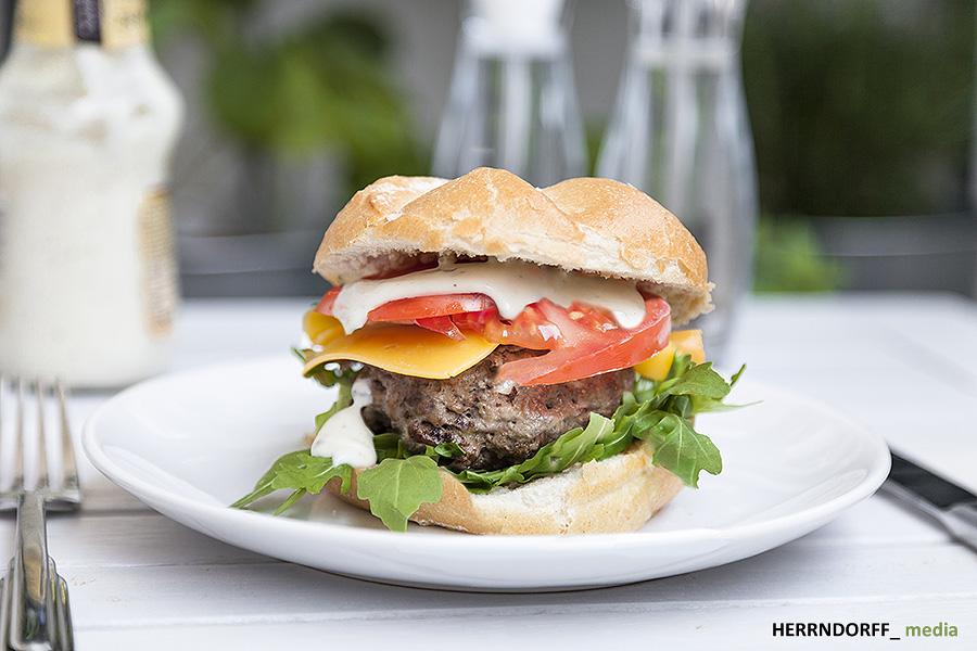Hamburger aus Rindfleisch mit Rucola Cheddarkäse, Tomatenscheiben und duftender Knoblachsoße