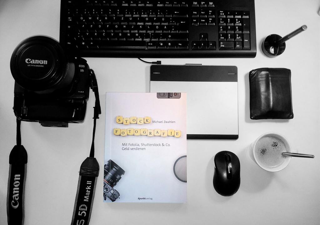 Blick auf den Arbeitsplatz eines Stockfotografen mit dem neuen Buch von Michael Zwahlen in der Bildmitte
