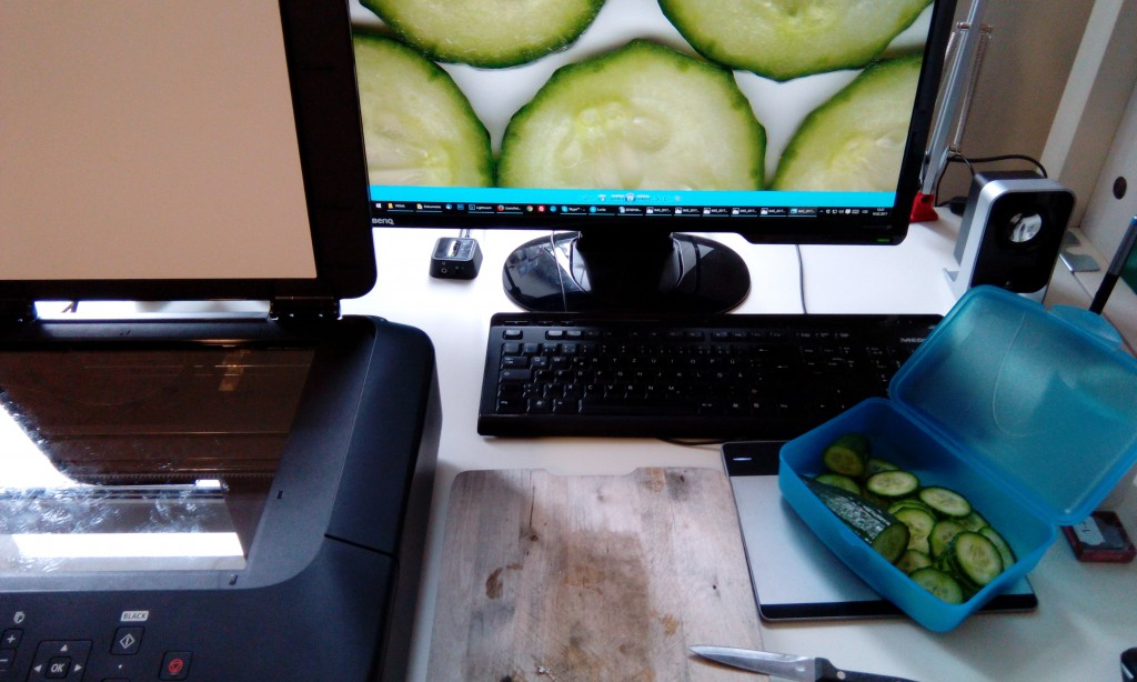 Mein Schreibtisch mit Scanner, Schneidbrett, Gurken und Monitor