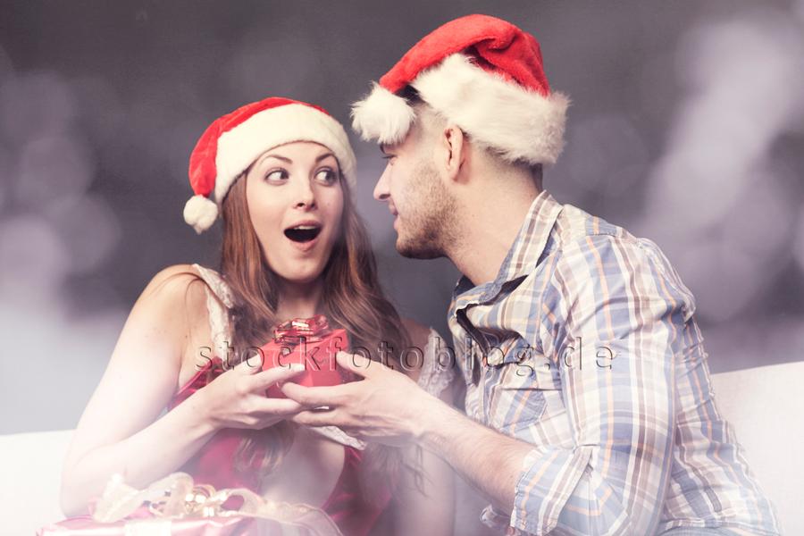Junges Paar mit Weihnachtsmannmützen auf dem Sofa schenkt sich etwas am Heiligabend