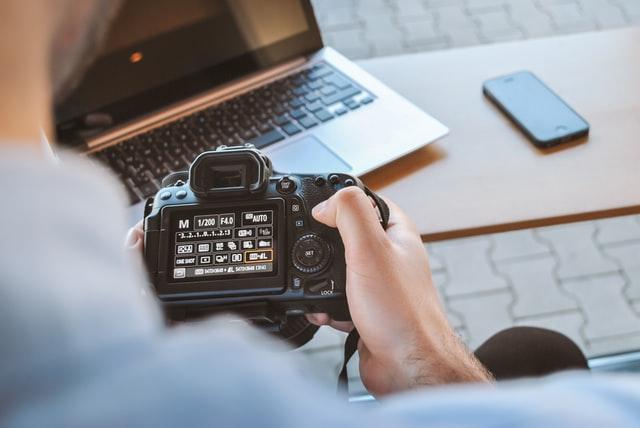 Blick über die Schulter eines Fotografen auf einen Fotoapparat